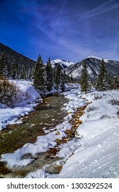 Mountain valley with water flowing in river and cover of freshly fallen snow on sunny blue sky day