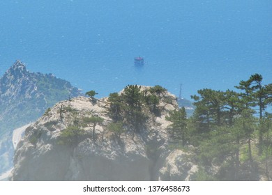 Mountain view of the black sea coast. Dawn in Crimea and fog in the mountains. The oil platform is far out to sea. Pine forest on the rocks in Russia.