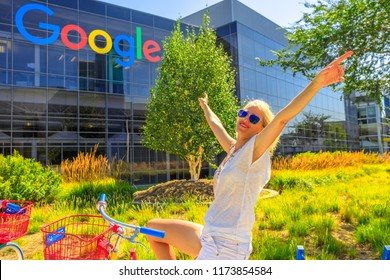 Mountain View, California, USA - August 13, 2018: Smiling tourist woman on Google bike under Google sign at Google Headquarters building. A young girl visiting the web leader company in Silicon Valley