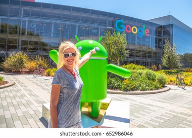 Mountain View, California, USA - August 15, 2016: Smiling woman showing Google sign on facade of Google Headquarters building. Young tourist visiting popular technology company in Silicon Valley.