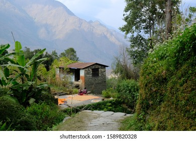 Mountain view with house and silhouette of nepali women sitting by blanket with drying grain in sunny and cloudy day. During trekking around Ghorepani. Himalayas, Nepal