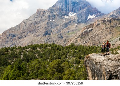 Mountain view men staying on high Rock Peaks Cloudy Sky on Background Forest Stone Hikers Female