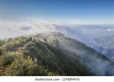 Mountain view misty morning of the mist moving up around the high mountain with blue sky background, sunrise at top of Doi Pha Hom Pok National Park, Fang, Chiang Mai, northern Thailand.