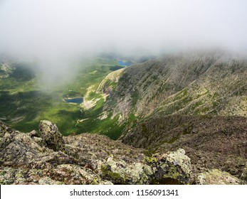 Mountain view, rocky slopes dropping into lush valley under low clouds, mountain pond.  A view of Katahdin's Chimney Pond from along the Knife's Edge in Baxter State Park.