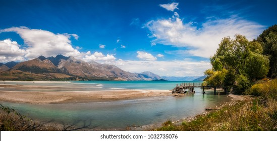 Mountain View and wooden piers at Kinloch, an unspoiled and remote touristic site located where Dart river is flowing into the Northern end of Lake Wakatipu in Otago Region, New Zealand, South Island.