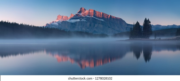 The mountain views when you are in Two Jack Lake campground of Banff National Park in Alberta, Canada. Beautiful morning durin autumn time. Nature background concept.