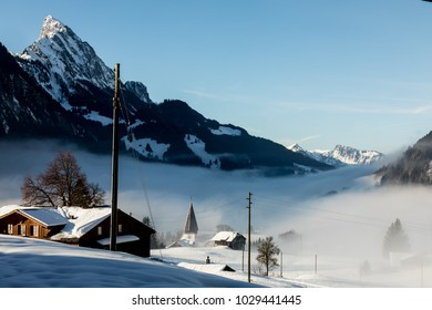 Mountain Village in the Alps Covered with Snow and Clouds