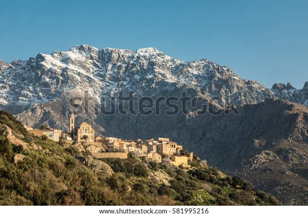 Mountain village of Montemaggiore in the Balagne region of Corsica with a snow capped Monte Grosso mountain behind and clear blue sky