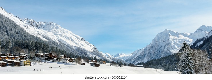 A mountain village with wooden house and snow covered mountains in background