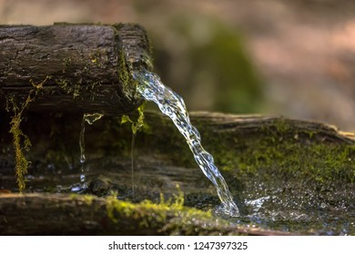 Mountain water spring out of wooden gutter from rocky creek
