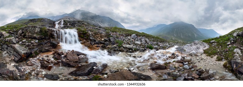 Mountain waterfall stream in misty rainy weather in the valley flowers. Cylindrical panorama 360