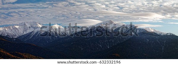 Mountain winter landscape at sunset with lenticular clouds over high snow-capped peaks. Caucasus. Russia. The Caucasian reserve. View from Mount Kazachya
