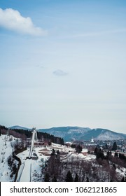 Mountain wintersport scenery with ski-jump under blue cloudy sky. Winterberg, Germany.