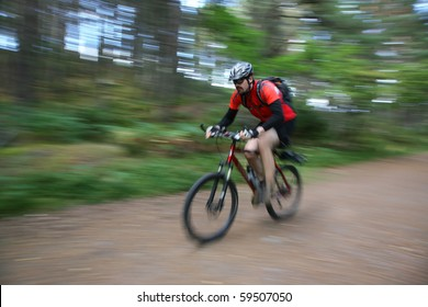 A mountainbiker in a forest in aviemore, scotland. Face is sharp, rest has got motion blur.