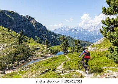 Mountainbiker on fast downhill driving on mountain Reiteralm to Lake Spiegelsee with mountain Dachstein in the background