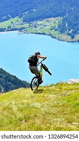 A mountainbiker on a scenic downhill ride above Lake Reschen in Trentino - Alto Adige in Italy