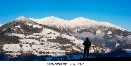 Mountaineer in backlight with snowy mountains in the background, Zegama, Basque Country