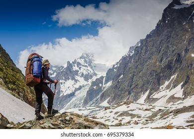 Mountaineer with backpack on the trail