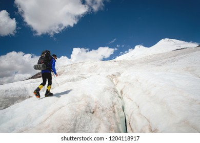 A mountaineer with a backpack walks in crampons walking along a dusty glacier with sidewalks in the hands between cracks in the mountain
