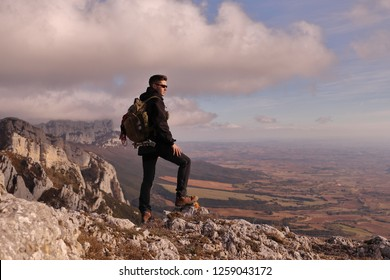 MOUNTAINEER BOY  WITH BACKPACK AND SUNGLASSES REACHING THE SUMMIT OF A HIGH MOUNTAIN