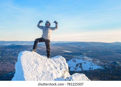 The mountaineer climbed the mountain top, man hiker standing at the peak of rock and celebrates the success.