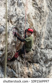 A mountaineer, climber or cave explorer in full outfit (helmet, safety system, carabiners etc) lays a route on a rock