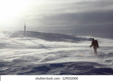 Mountaineer climbing the snowy mountain in stormy winds, Romania