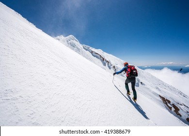 Mountaineer climbs snowfield on a sunny day high on a mountain.
