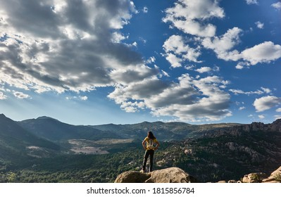 A mountaineer contemplates La Pedriza from the top of a rock in the Sierra de Guadarrama National Park. Madrid's community. Spain.