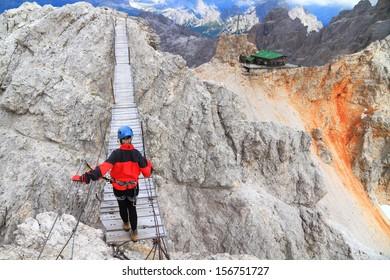 Mountaineer crossing the suspension bridge on Monte Cristallo, Dolomite Alps, Italy