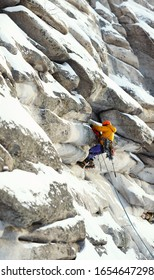 Mountaineer figure in bright outfit climbing up during the winter ascent in the mountains, against the background of overhanging rocks in the foreground and background are out of focus, panorama.