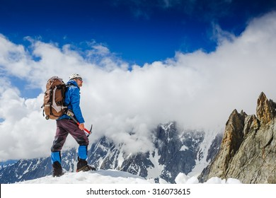 Mountaineer with ice ax reaches the top of a snowy mountain in a sunny winter day