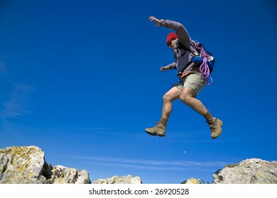 A mountaineer jumping trough the rocks, over a clear blue sky