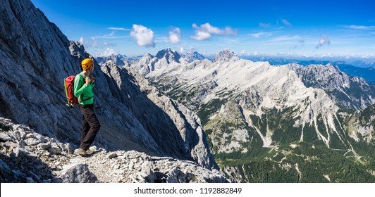 Mountaineer just below the top of the Prisojnik mountain in Julian Alps enjoying the view