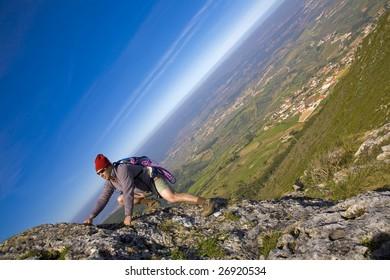 A mountaineer man, climbing a steep cliff
