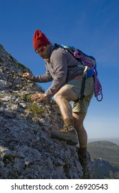 A mountaineer man, climbing a steep cliff