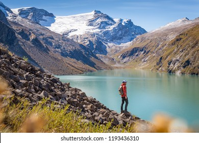 Mountaineer with mountain lake and snow capped mountains