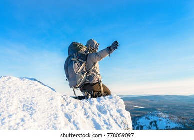 The mountaineer at the mountain top covered with ice and snow, man hiker sitting at the peak of rock and celebrates the success and amazing view from high altitude.