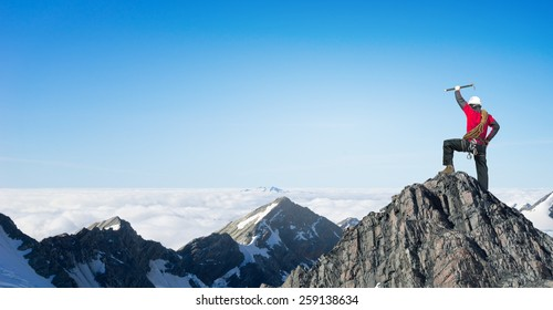 Mountaineer at peak of mountain enjoying natural landscape