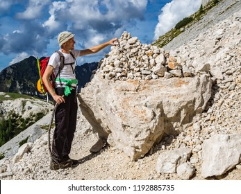 The mountaineer placing a stone on a stone pile by the path under the Prisojnik mountain, Slovenia