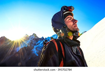 Mountaineer reaches the top of a snowy mountain. Extreme sport concept