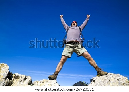 A mountaineer reaching the summit, and shouting with joy, for his achievement