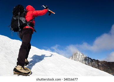 Mountaineer reaching the top of a snowcapped mountain peak,  Mt. Grivola, west italian alps, Europe. Horizontal frame.