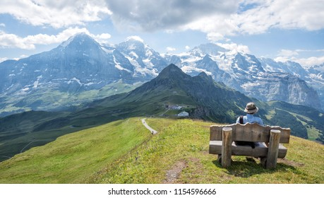 mountaineer resting at wooden bench, enjoying the view to eiger, monch and jungfrau. famous peaks at bernese oberland, swiss alps