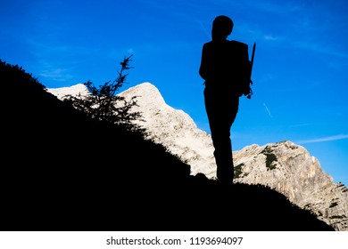 Mountaineer silhouette on the slope of the Prisank mountain looking at the Mojstrovka mountain, Slovenia