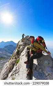 Mountaineer sitting resting on the mountain ridge on the path to Skuta mountain in Kamnik-Savinja Alps, Slovenia