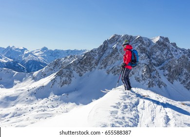 Mountaineer with skiers enjoying the view in the mountains in winter