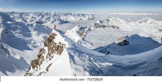 Mountaineer standing on a snow capped mountain summit in the alps