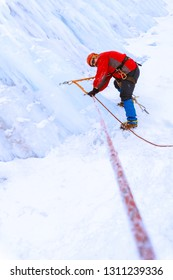 mountaineer traversing the ice wall of a glacier during snowfall