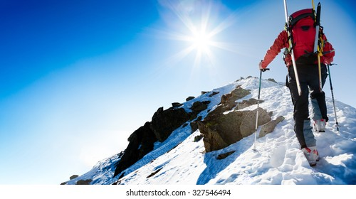 Mountaineer walking up along a snowy ridge with skis in the backpack. In background blue sky and shiny sun. Concepts: adventure, determination, extreme sport. Large copy-space on the left for text.